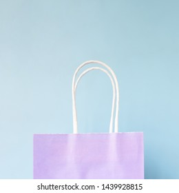 Hand holding paper bag on flat color background