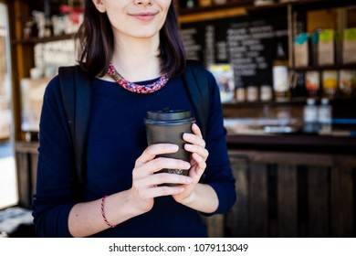 hand holding a paper black cup on the background of a cafe. concept of cheerfulness, coffee break