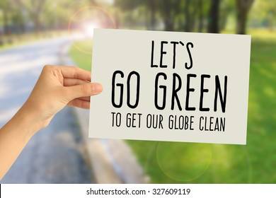 Hand holding a paper card with Let's go green to get our globe clean word on abstract nature background