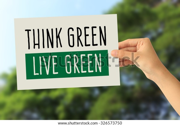 Hand holding a paper card with Think green, Live green word on abstract nature background
