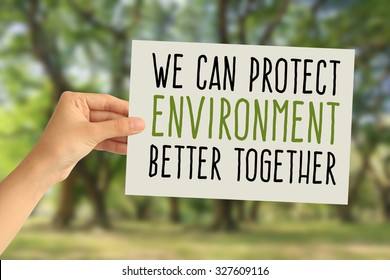 Hand holding a paper card with We can protect environment better together word on abstract nature background