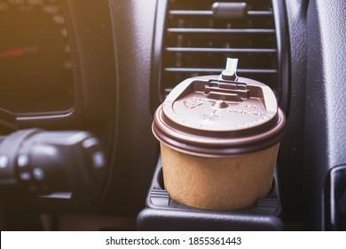 Hand, die am Morgen eine Kaffeetasse Papier hält, während sie ein Auto fährt.