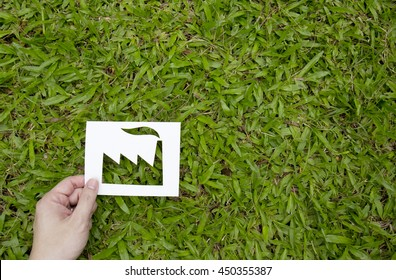Hand holding paper cut in factory shape on green grass.Eco friendly green living