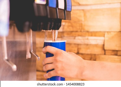 hand holding a paper glass to pour the lemonade soda soft drink  machine  in a fastfood restaurant