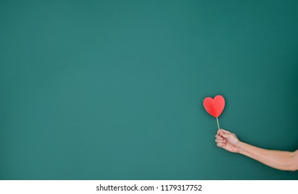Hand holding paper heart in front of green chalkboard.