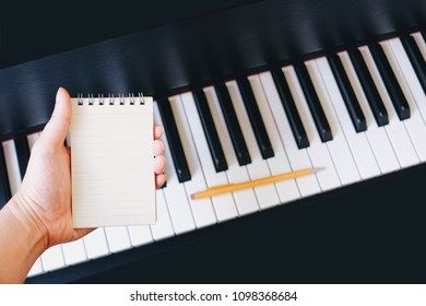 Hand holding paper note can add text , piano background