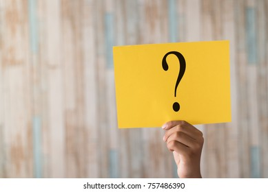 hand holding a paper note with question mark.question mark written on paper