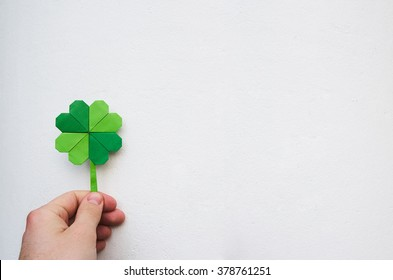 Hand holding paper origami green shamrock on white wall background. Space for copy, lettering, text. St. Patrick's day postcard template.