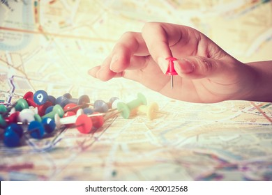 hand holding paper pin with blur pile of pins on map