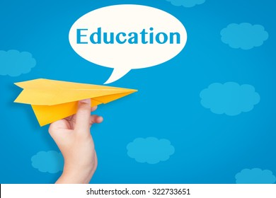 hand holding paper plane with education in speech bubble on blue background