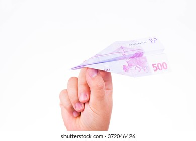 A hand holding a paper plane made with a 500 euro note on white background