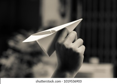 A hand holding the paper plane with ready for throw position. Black and white image. Follow the dream concept.