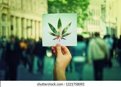 Hand holding a paper sheet with marijuana leaf symbol over a crowded street background. Cannabis legalization as medical drug. CBD healing social issue concept.