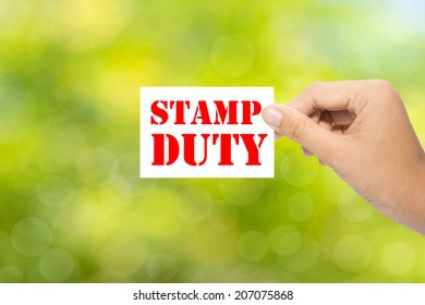 Hand holding a paper STAMP DUTY on green background