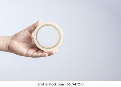 Hand holding paper tape roll on white background