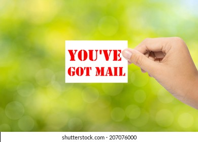 Hand holding a paper YOU'VE GOT MAIL on green background