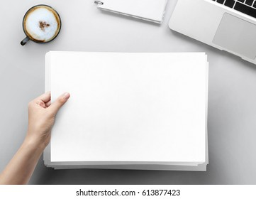 Hand holding papers a4 size on paper at white office desk table top view with copy space
