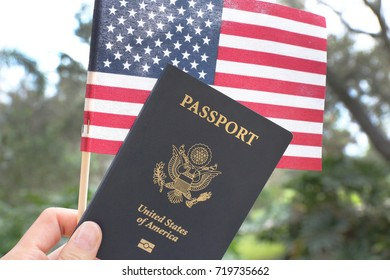 Hand holding passport and American flag