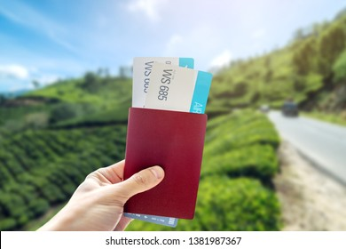 Hand holding a passport and two air tickets on a background of tea plantations. The concept of travel and vacation in beautiful places