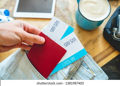 Hand holding a passport and two tickets on the background of the camera, the world map, the plane. The concept of preparing for the journey to meet adventures