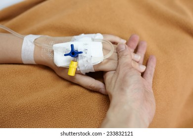 Hand holding patient hand in the hospital