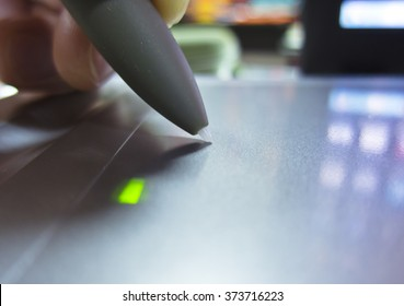 Hand holding a pen and draws on the graphic tablet glows green light reflection labels on laptop computer
