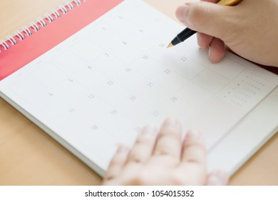 hand holding pen and marking on calendar
