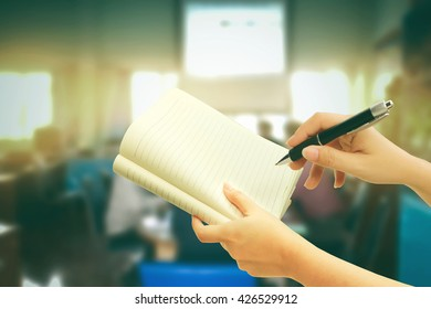 hand holding pen and notepad with blur people in meeting room background