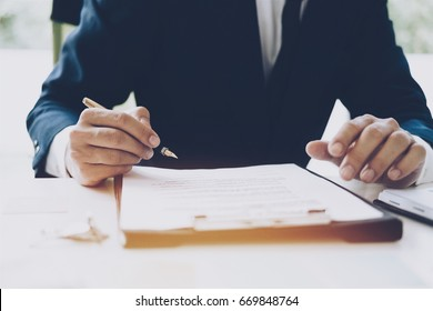 Hand holding pen for signature, business