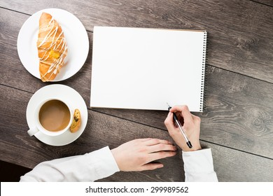 hand holding a pen. Top view. Table with notepads, cup of coffe and croissant . empty white space you can put your text.