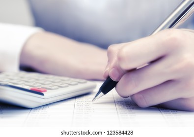 Hand is holding pen and writing in chart with ready calculator