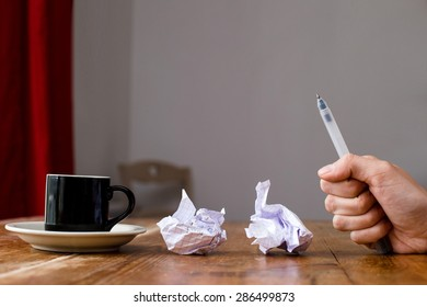 A hand holding a pen writing in his fist, frustrated failure in creativity and work. Crumpled paper coffee cup on a wooden table.