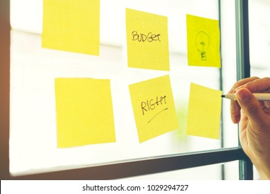 Hand holding pen and writing on sticky note papers which are on mirror wall. Wording Budget, Right and drawing lamps are on note paper and empty. Brainstorming teamwork to write financial keyword