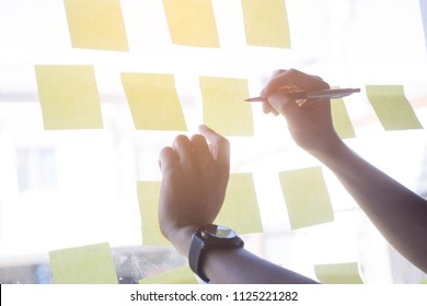 Hand holding pen and writing on sticky note papers which are on mirror wall. Business man writing on adhesive notes in creative office.selective focus