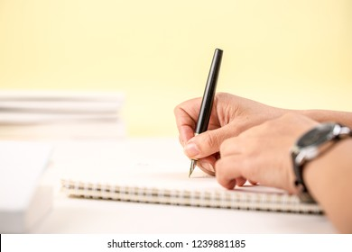 Hand holding pen writing on notebook
