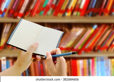 hand holding pencil and notebook with blur bookshelf background