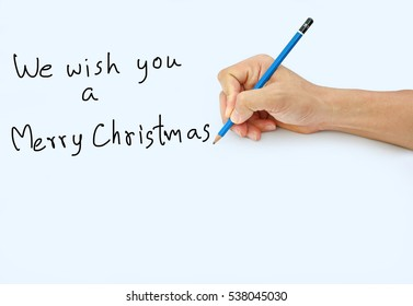 """Hand holding a pencil on a white paper background, writing with pencil for word """" We wish you a Merry Christmas """""""