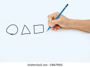 Hand holding a pencil on a white paper background, Drawing with pencil for image shape of Circle Triangle and Square