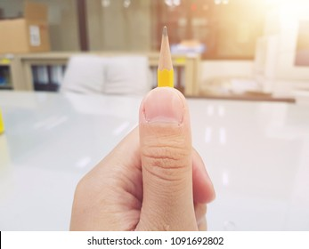 Hand holding a pencil with white paper sheet on table in meeting room