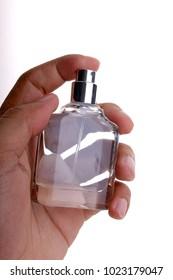 Hand holding perfume on white background