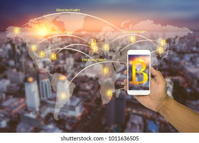 Hand holding a phone with bitcoins and block chains and connexions with people and world map on city background