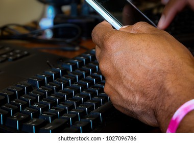 Hand holding a Phone with Keyboard in the background