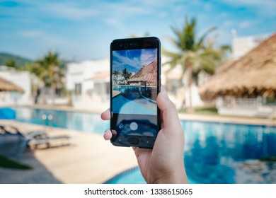 hand holding phone on background of the pool in hotel. photo camera on the screen. close up hand hold smartphone take a picture of summer vacation