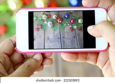 Hand are holding the phone to take photos of Christmas decorations