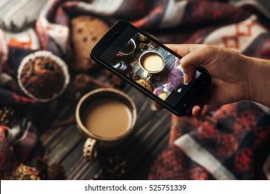 手拿手机拍摄时尚的冬季平躺咖啡饼干和香料木质乡村背景的照片。舒适的心情秋天。Instagram 博客车间概念。