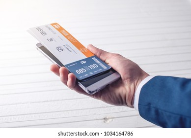 The hand holding the phone with the train tickets. The concept of online purchase and booking of tickets for travel using the site or application