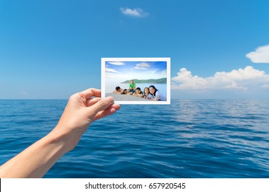 Hand holding a picture of happy big Asian family tourist on vacation with beautiful white clouds on blue sky over calm sea in background.