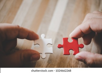 Hand holding piece of blank jigsaw puzzle with wooden table background.