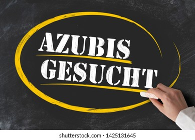 hand holding piece of chalk against blackboard with text AZUBIS GESUCHT, German for apprentices or trainees wanted
