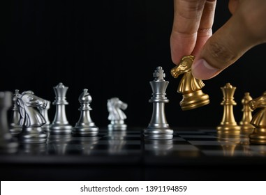 Hand holding a piece of chess (knight or horse) to win the game on black background. Checkmate, success, business strategy, tactics, win, victory, winner concept.